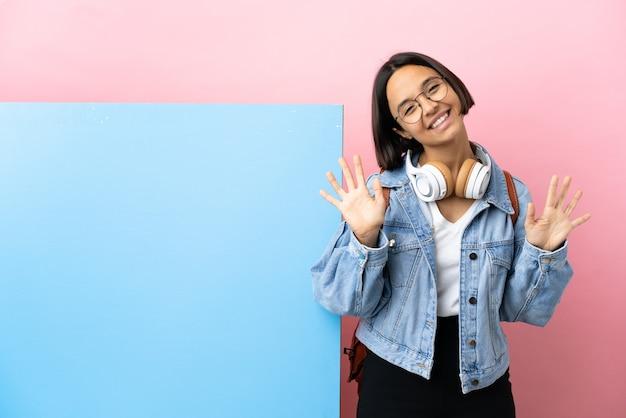 Mulher jovem estudante mestiça com um grande banner sobre fundo isolado contando dez com os dedos