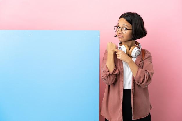 Mulher jovem estudante mestiça com um grande banner sobre fundo isolado fazendo o gesto de estar atrasado