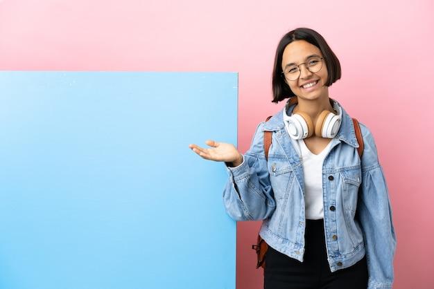Mulher jovem estudante mestiça com um grande banner sobre um fundo isolado apresentando uma ideia enquanto olha sorrindo para