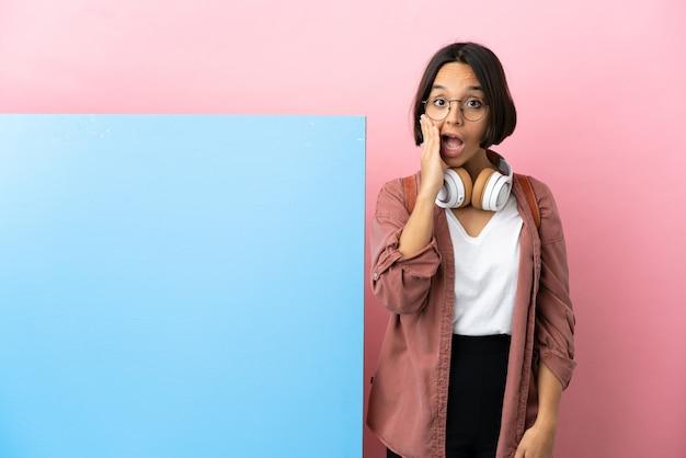 Mulher jovem estudante mestiça com um grande banner sobre um fundo isolado com expressão facial surpresa e chocada