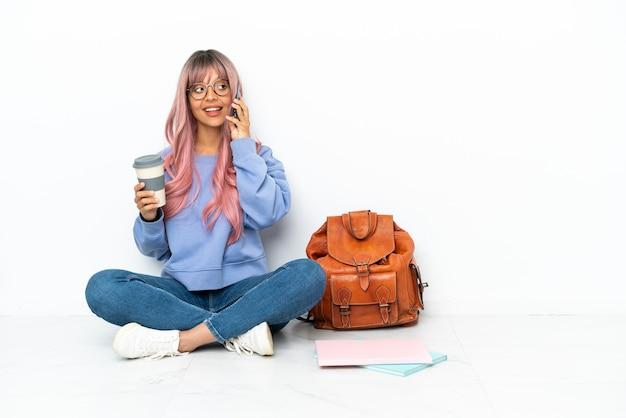 Mulher jovem estudante mestiça de cabelo rosa sentada no chão, isolado no fundo branco, segurando um café para levar e um celular