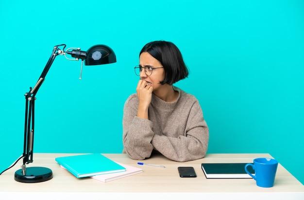 Mulher jovem estudante mestiça estudando em uma mesa nervosa e assustada