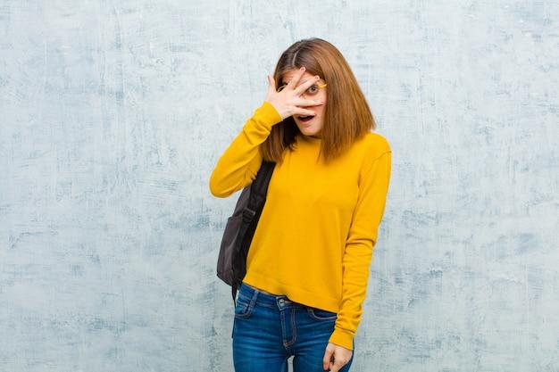 Mulher jovem estudante olhando chocado, assustado ou aterrorizado, cobrindo o rosto com a mão e espreitar entre os dedos contra o fundo da parede grunge