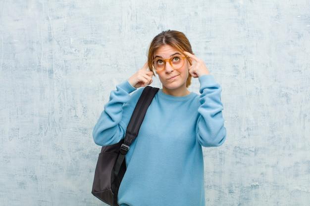 Mulher jovem estudante olhando concentrado e pensando seriamente em uma idéia, imaginando uma solução para um desafio ou problema