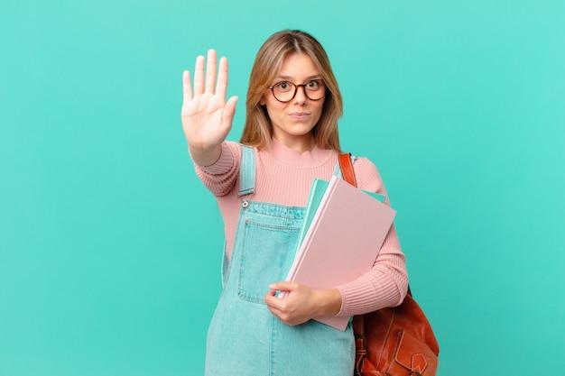 Mulher jovem estudante olhando séria, mostrando a palma da mão aberta fazendo gesto de pare
