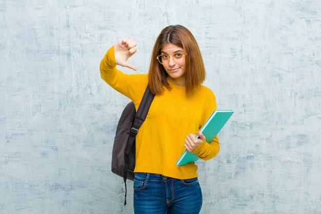 Mulher jovem estudante olhando triste, decepcionado ou com raiva, mostrando os polegares para baixo em desacordo, sentindo-se frustrado contra o fundo da parede grunge