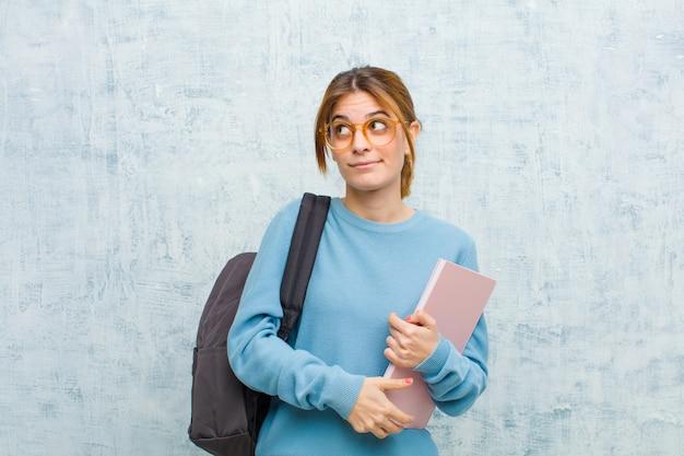 Mulher jovem estudante pensando, pensando felizes pensamentos e idéias, sonhando acordado, olhando para copiar o espaço do lado na parede do grunge