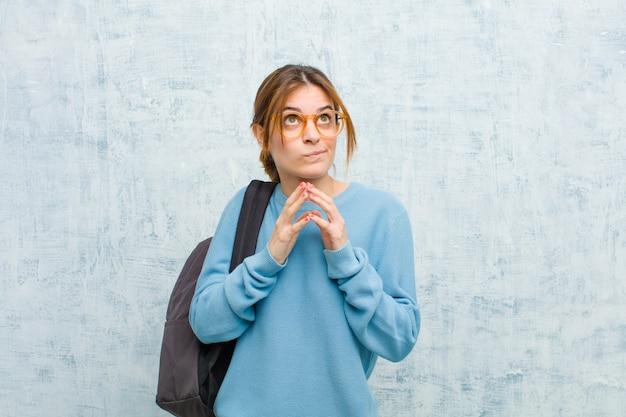 Mulher jovem estudante planejando e conspirando, pensando truques e truques tortuosos, astúcia e traição contra a parede da parede do grunge