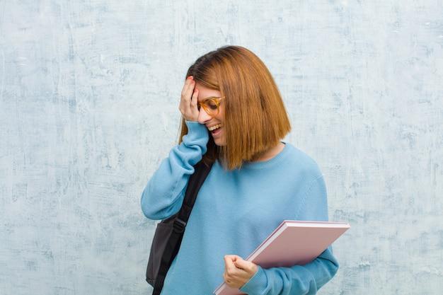 Mulher jovem estudante rindo e batendo na testa