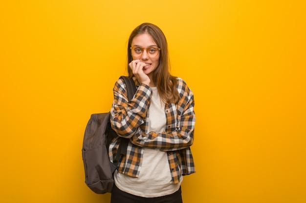 Mulher jovem estudante roer unhas, nervoso e muito ansioso