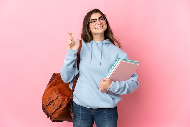 Mulher jovem estudante rosa com os dedos se cruzando e desejando o melhor