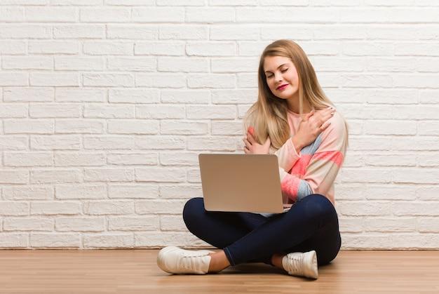 Mulher jovem estudante russo sentado dando um abraço