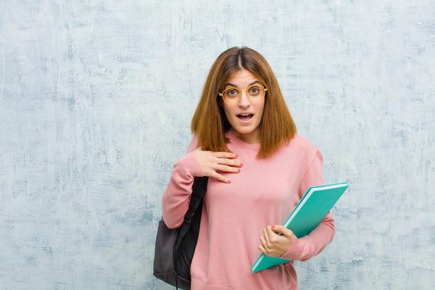 Mulher jovem estudante se sentindo chocada, surpresa e surpresa, com a mão no peito e a boca aberta, dizendo quem, eu? contra o fundo da parede grunge