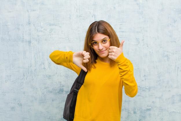 Mulher jovem estudante se sentindo confuso, sem noção e inseguro, ponderando o bem e o mal em diferentes opções ou escolhas contra a parede do grunge