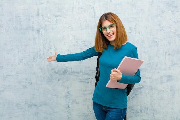 Mulher jovem estudante se sentindo feliz e alegre, sorrindo e dando as boas-vindas, convidando-o com um gesto amigável