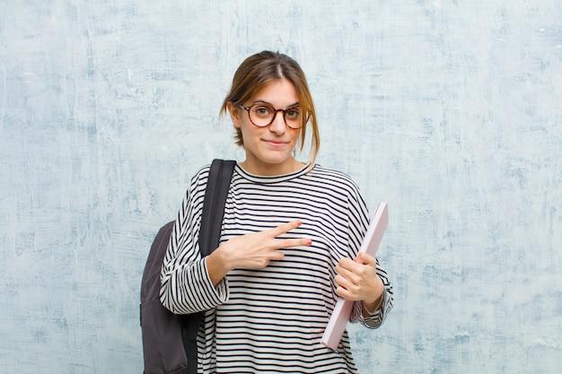 Mulher jovem estudante se sentindo feliz, positivo e bem sucedido, com a mão fazendo v forma sobre o peito, mostrando vitória ou paz