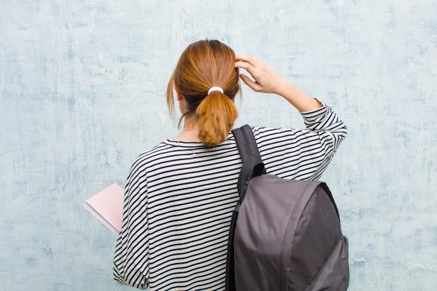 Mulher jovem estudante se sentindo sem noção e confuso pensando uma solução com a mão no quadril e outro na cabeça vista traseira