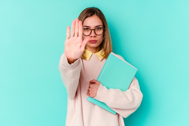 Mulher jovem estudante segurando livros isolados em um fundo azul em pé com a mão estendida, mostrando o sinal de stop, impedindo-o.