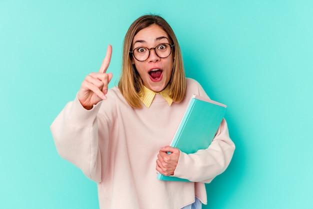 Mulher jovem estudante segurando livros isolados em um fundo azul, tendo uma ideia, o conceito de inspiração.