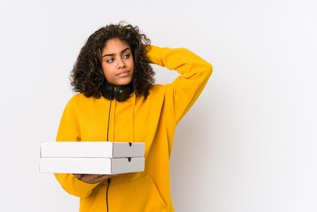 Mulher jovem estudante segurando pizzas tocando a parte de trás da cabeça, pensando e fazendo uma escolha.