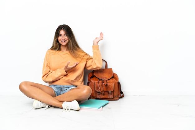 Mulher jovem estudante sentada no chão com um laptop isolado no fundo branco, estendendo as mãos para o lado para convidar para vir