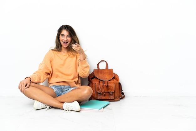 Mulher jovem estudante sentada no chão com um laptop isolado