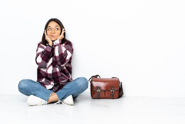 Mulher jovem estudante sentada no chão frustrado e cobrindo as orelhas