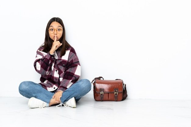 Mulher jovem estudante sentada no chão, mostrando um sinal de gesto de silêncio colocando o dedo na boca