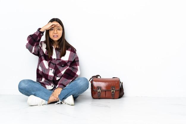 Mulher jovem estudante sentada no chão olhando para longe com a mão para procurar algo
