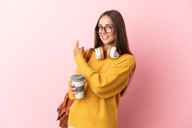Mulher jovem estudante sobre fundo rosa isolado apontando para trás