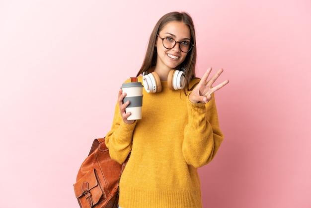 Mulher jovem estudante sobre fundo rosa isolado feliz e contando três com os dedos