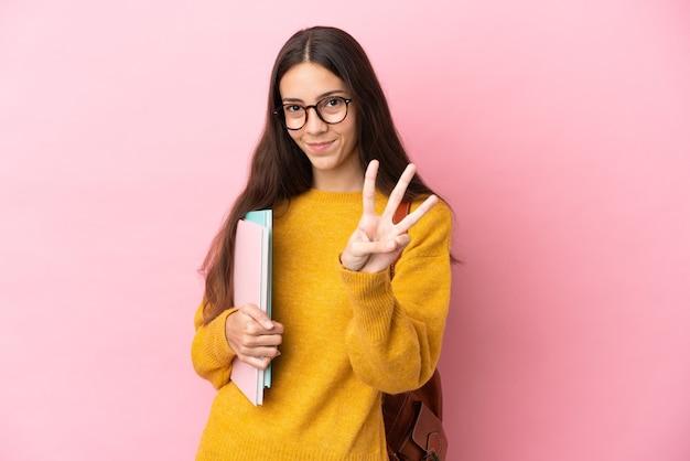 Mulher jovem estudante sobre um fundo isolado feliz e contando três com os dedos