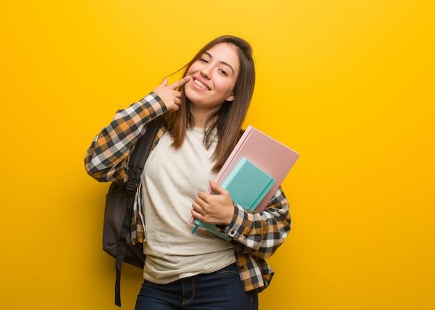 Mulher jovem estudante sorri, apontando a boca