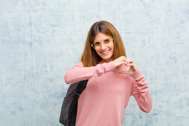 Mulher jovem estudante sorrindo e se sentindo feliz, fofo, romântico e apaixonado, fazendo formato de coração com as duas mãos contra a parede da parede de grunge