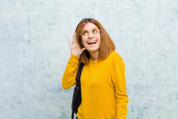Mulher jovem estudante sorrindo, olhando curiosamente para o lado, tentando ouvir fofocas ou ouvir um plano secreto