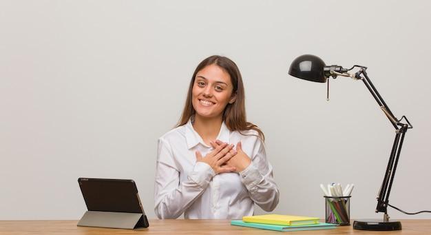 Mulher jovem estudante trabalhando em sua mesa fazendo um gesto romântico