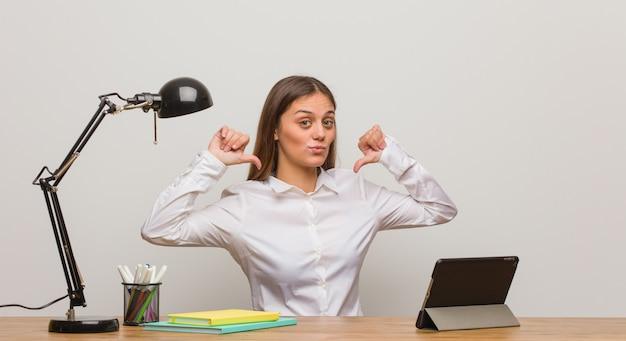 Mulher jovem estudante trabalhando na mesa dela apontando os dedos, exemplo a seguir