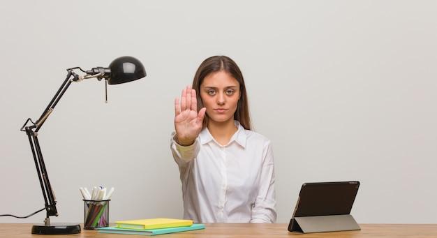 Mulher jovem estudante trabalhando na mesa dela colocando a mão na frente
