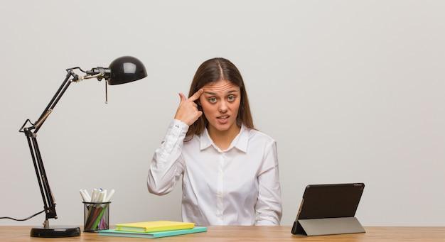 Mulher jovem estudante trabalhando na mesa dela fazendo um gesto de decepção com o dedo