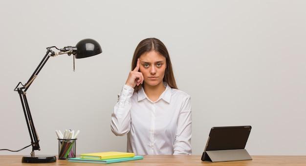 Mulher jovem estudante trabalhando na mesa dela pensando em uma idéia