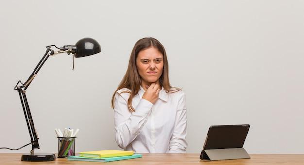 Mulher jovem estudante trabalhando na mesa dela tossir, doente devido a um vírus ou infecção