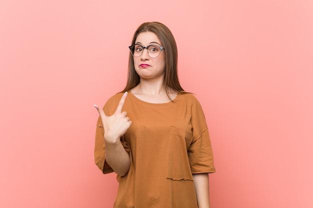 Mulher jovem estudante usando óculos, apontando com o dedo para você, como se estivesse convidando para se aproximar