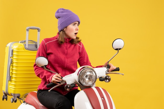 Mulher jovem estupefata em uma motocicleta olhando para algo de frente