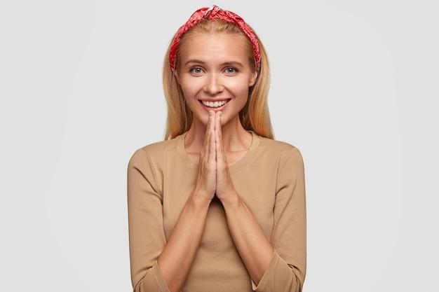 Mulher jovem europeia feliz com cabelo loiro, mantém as mãos em gesto de oração