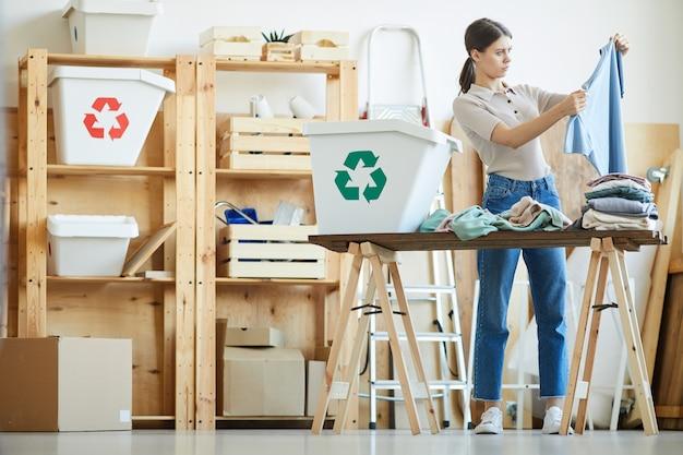 Mulher jovem examinando suas roupas velhas e classificando-as em recipientes de plástico especiais