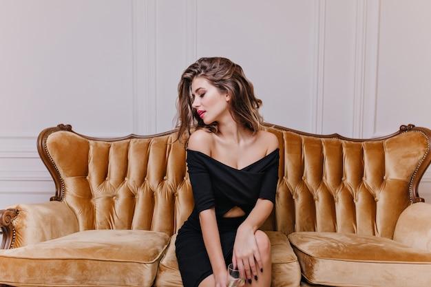 Mulher jovem, excêntrica e interessante de 25 anos, sentada em uma grande cadeira real e posando, contra uma parede branca como a neve