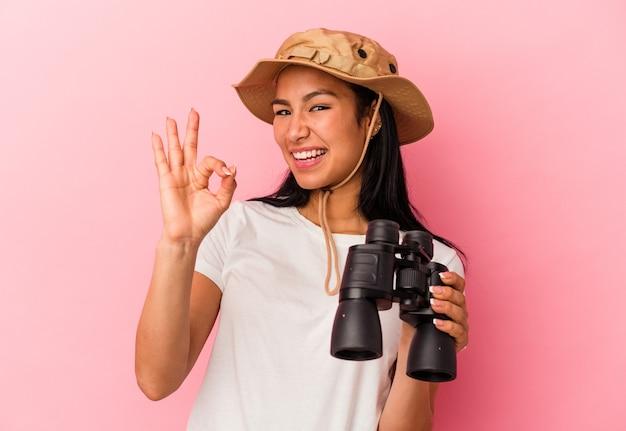 Mulher jovem explorador de raça mista segurando binóculos isolados no fundo rosa alegre e confiante, mostrando o gesto ok.