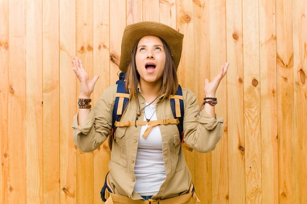 Mulher jovem explorador latina contra a parede de madeira