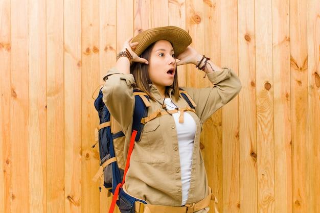 Mulher jovem explorador latino contra o fundo da parede de madeira