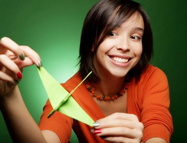 Mulher jovem expressão com pássaro de papel